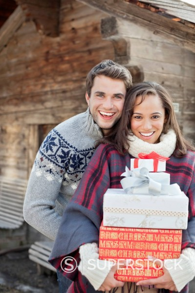 Stock Photo: 1775R-31161 Portrait of smiling couple holding Christmas gifts in front of cabin