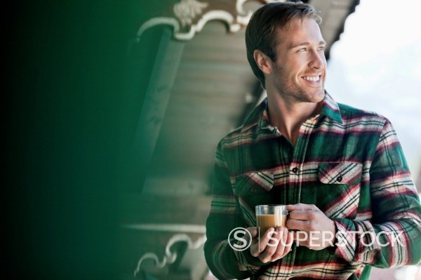 Stock Photo: 1775R-31162 Smiling man drinking coffee on cabin porch