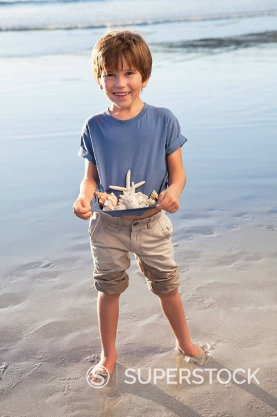Portrait of smiling boy holding seashells in shirt on beach : Stock Photo