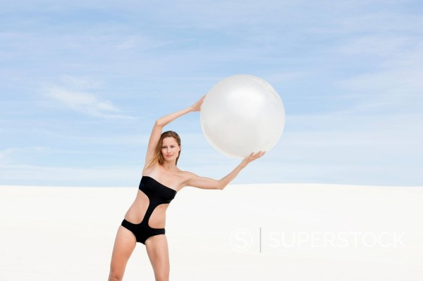 Portrait of woman in bathing suit stretching with fitness ball overhead : Stock Photo