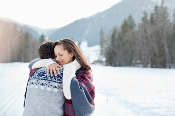 Smiling woman hugging man in snowy field : Stock Photo