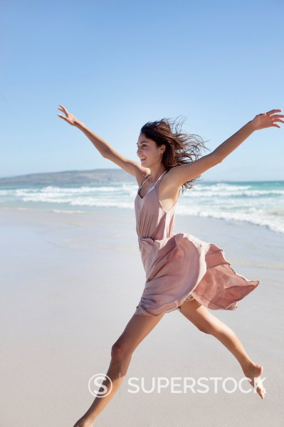 Stock Photo: 1775R-31210 Exuberant woman running on beach with arms outstretched
