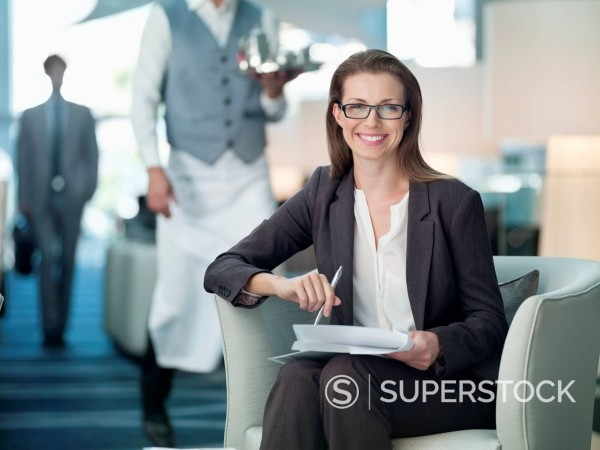 Portrait of smiling businesswoman working in hotel lounge : Stock Photo