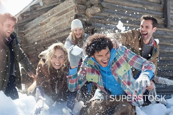 Friends enjoying snowball fight : Stock Photo