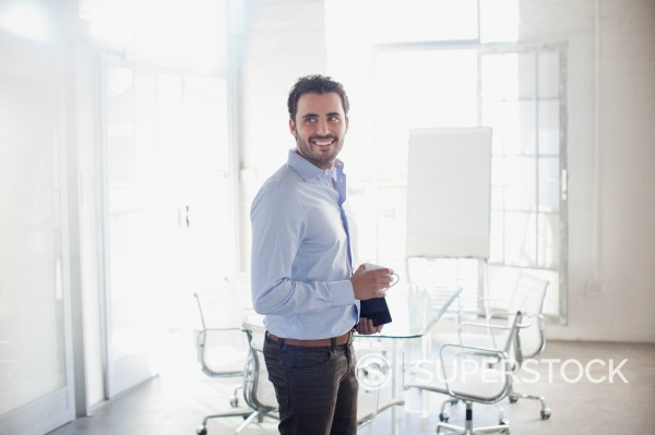 Smiling businessman holding coffee cup in conference room : Stock Photo