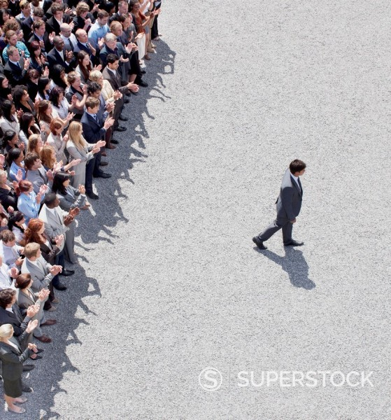 Stock Photo: 1775R-31230 Businessman walking away from clapping crowd