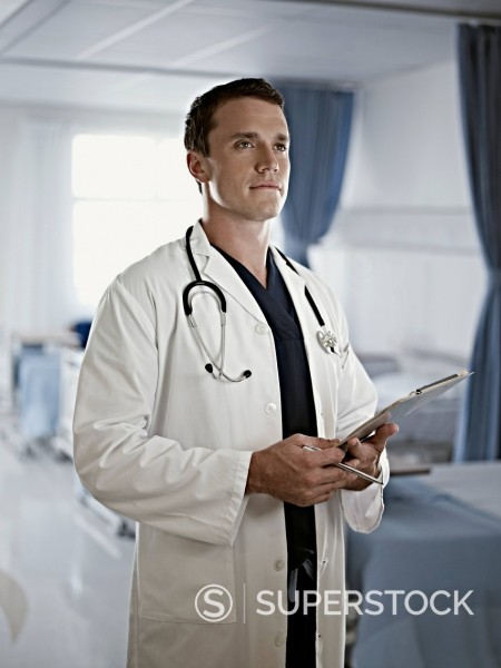 Portrait of confident doctor holding medical record in hospital room : Stock Photo
