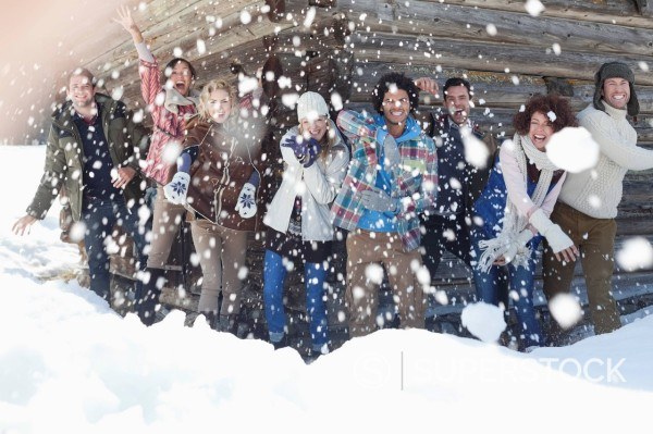 Stock Photo: 1775R-31247 Portrait of smiling friends throwing snowballs in front of cabin