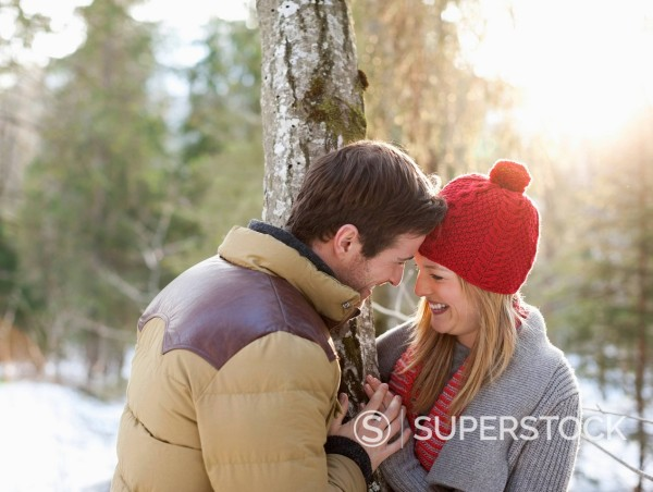 Stock Photo: 1775R-31248 Couple hugging face to face in snowy woods