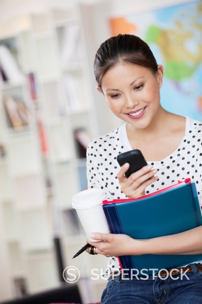 Stock Photo: 1775R-31268 Businesswoman with coffee and folders text messaging on cell phone