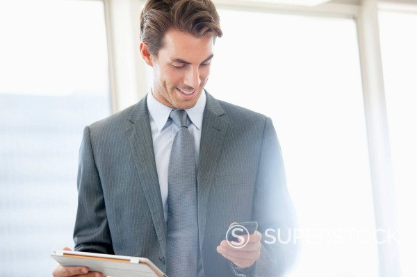 Smiling businessman holding digital tablet and checking cell phone : Stock Photo