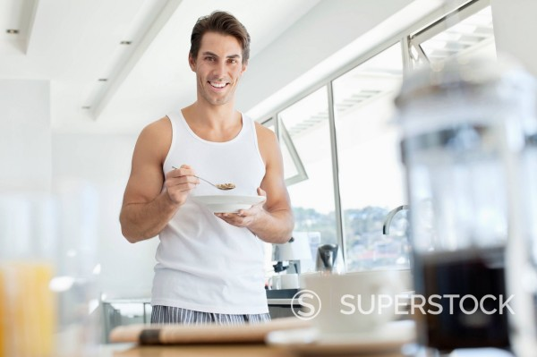 Stock Photo: 1775R-31273 Portrait of smiling man eating cereal in kitchen