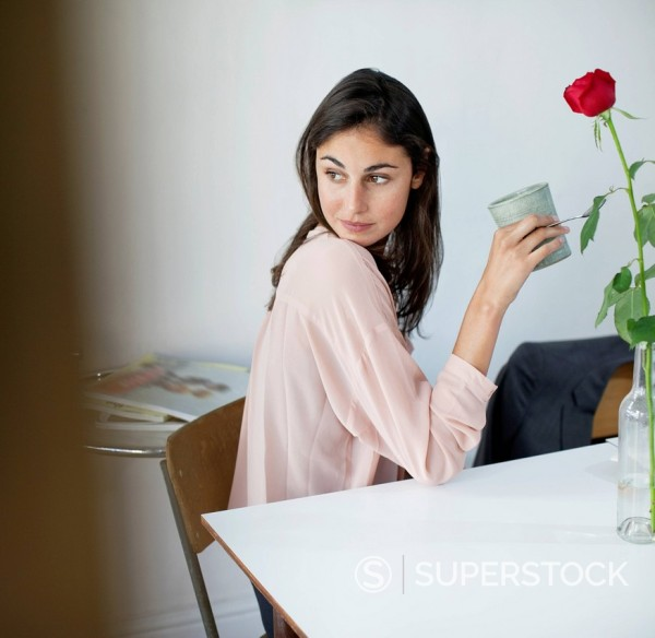 Woman at table drinking coffee and looking back : Stock Photo