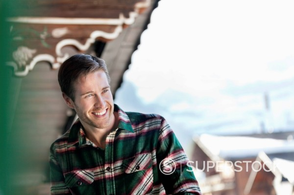 Man laughing on cabin porch : Stock Photo