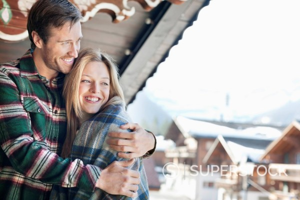 Stock Photo: 1775R-31278 Smiling couple hugging on cabin porch