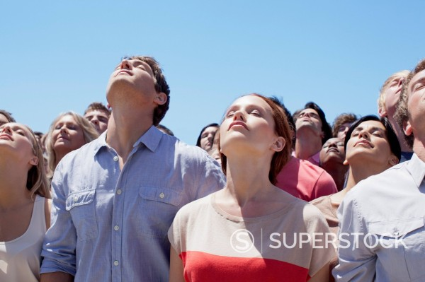 Serene people with heads back in crowd : Stock Photo