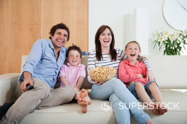 Stock Photo: 1775R-31304 Laughing family watching TV on sofa