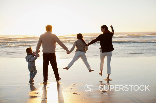 Stock Photo: 1775R-31306 Family holding hands on beach at sunset