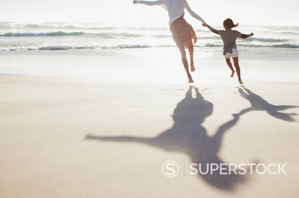 Stock Photo: 1775R-31325 Mother and daughter holding hands and running on sunny beach