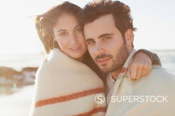 Portrait of couple wrapped in blanket and hugging on beach : Stock Photo