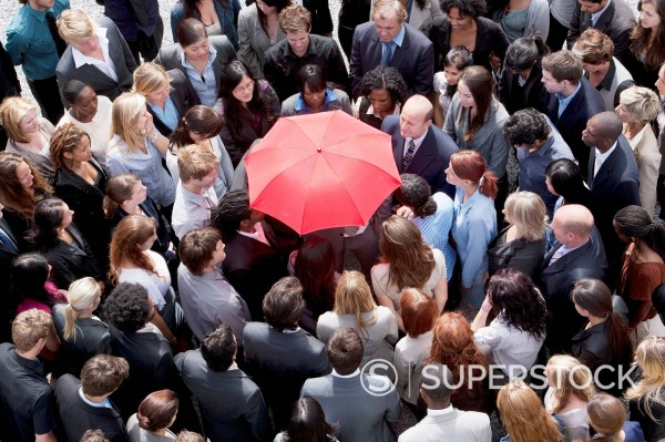 Stock Photo: 1775R-31355 Red umbrella at center of business people in huddle