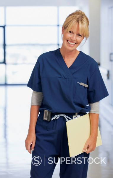 Stock Photo: 1775R-31371 Portrait of smiling nurse holding medical record in hospital corridor