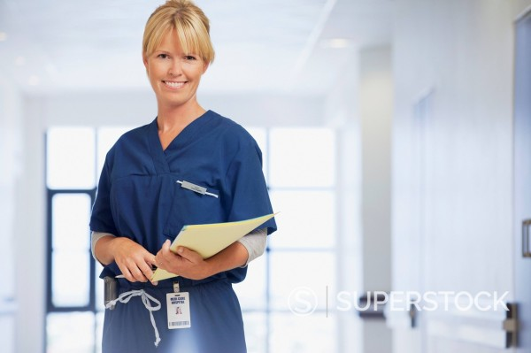 Stock Photo: 1775R-31372 Portrait of smiling nurse holding medical record in hospital corridor