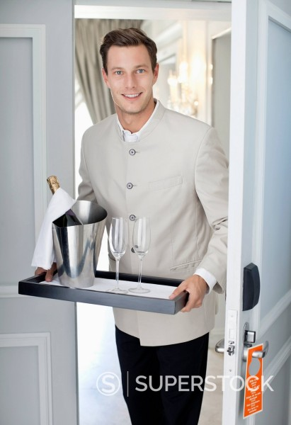 Stock Photo: 1775R-31374 Portrait of waiter in hotel room doorway with tray of champagne and glasses