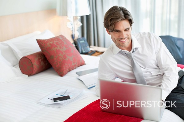 Stock Photo: 1775R-31375 Smiling businessman using laptop on bed in hotel room