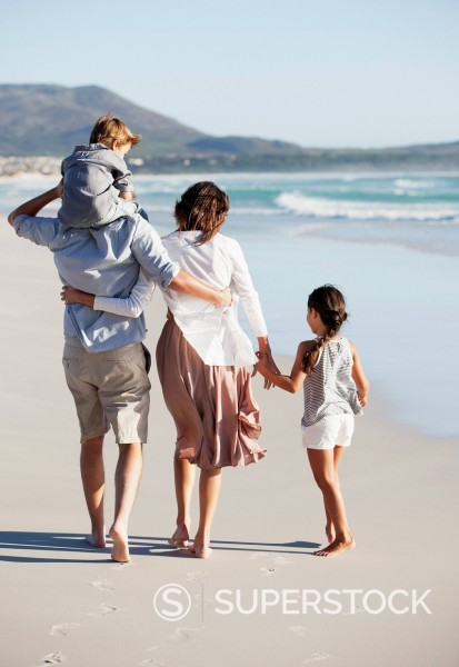 Family holding hands and walking on sunny beach : Stock Photo