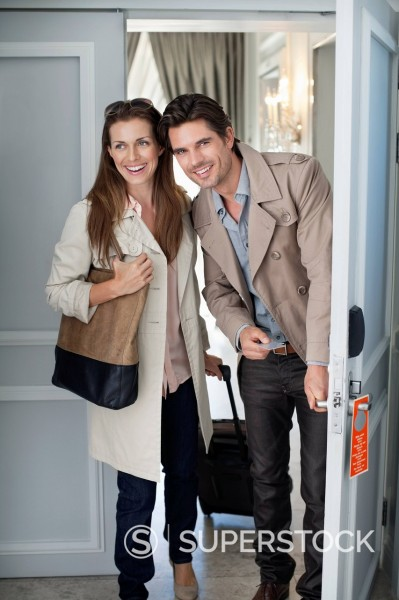 Smiling couple opening hotel room door : Stock Photo