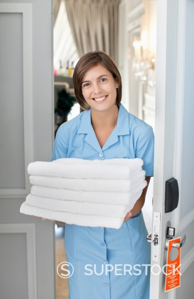 Portrait of smiling maid with towels in hotel room doorway : Stock Photo