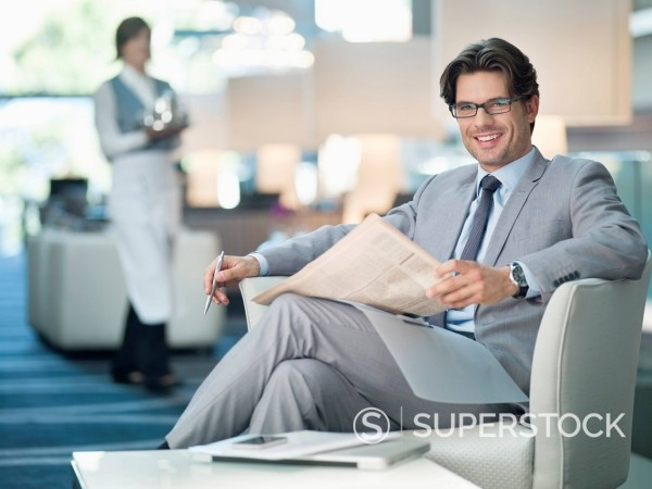 Portrait of smiling businessman reading newspaper in lounge : Stock Photo