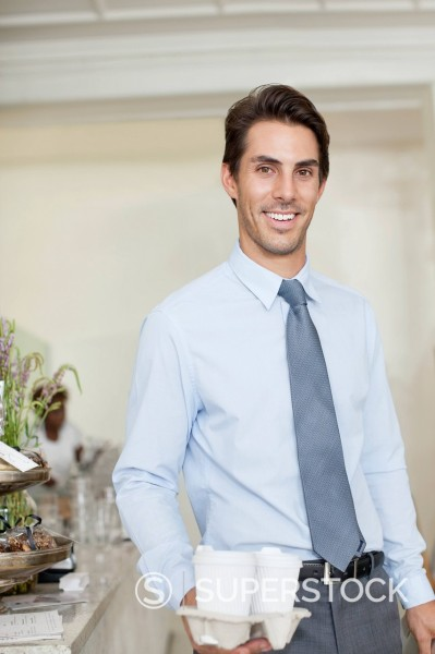 Stock Photo: 1775R-31418 Portrait of smiling businessman with take out coffee cups in cafe