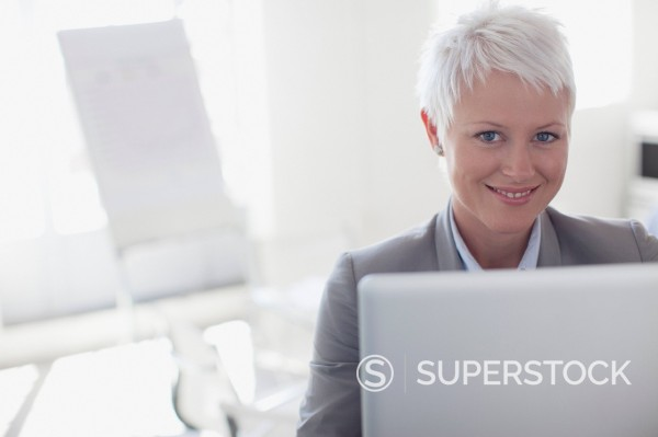 Portrait of smiling businesswoman working at laptop : Stock Photo