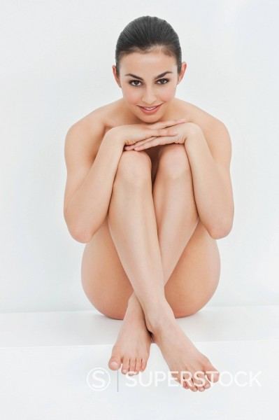 Stock Photo: 1775R-31444 Portrait of smiling nude woman hugging knees