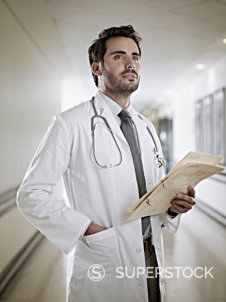 Stock Photo: 1775R-31452 Confident doctor holding medical record in hospital corridor