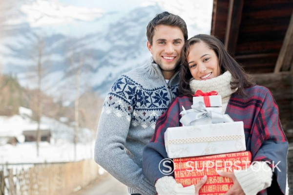 Portrait of smiling couple holding Christmas gifts : Stock Photo