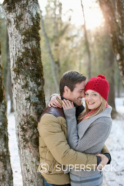 Portrait of smiling couple hugging in snowy woods : Stock Photo