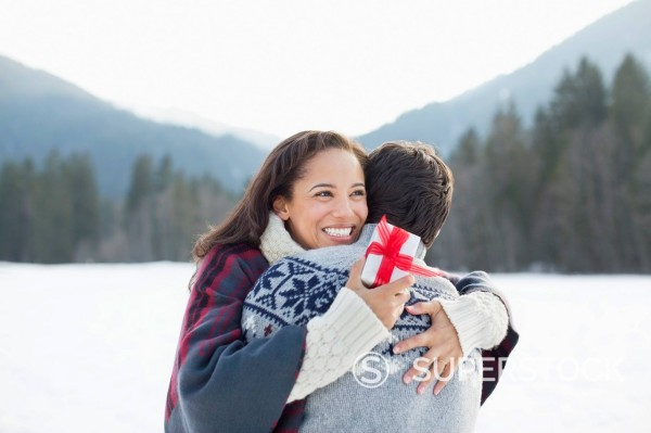 Smiling woman holding Christmas gift and hugging man in snow : Stock Photo