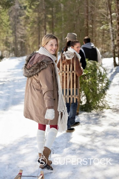 Stock Photo: 1775R-31480 Portrait of friends with sleds and fresh cut Christmas tree in woods