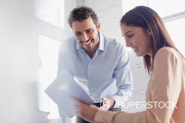 Smiling businessman and businesswoman using digital tablet in office : Stock Photo