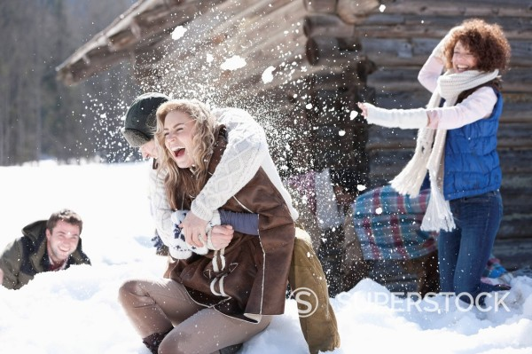 Stock Photo: 1775R-31507 Laughing friends enjoying snowball fight