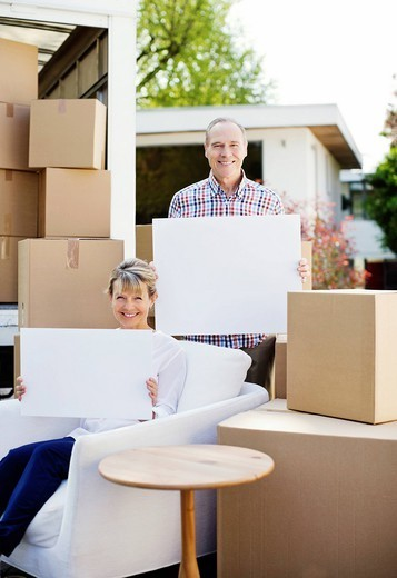 Couple sitting with moving boxes holding blank cards : Stock Photo