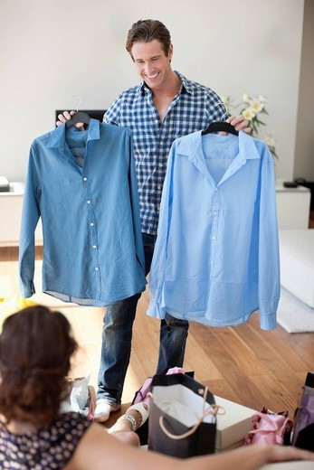 Man showing new shirts to wife : Stock Photo
