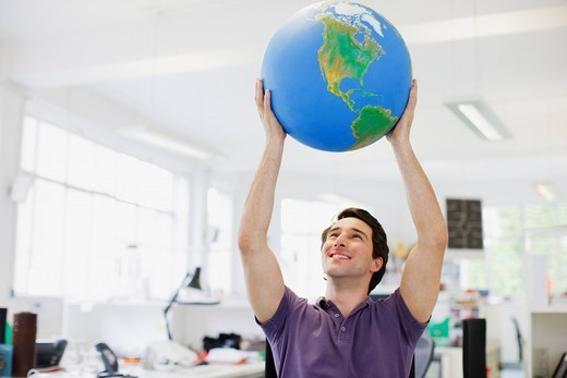 Smiling businessman lifting globe overhead in office : Stock Photo