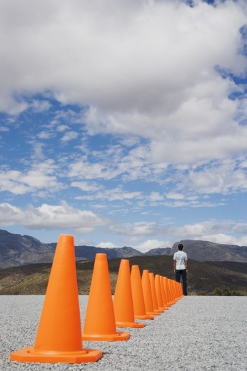 Man standing at the end of a row of safety cones : Stock Photo