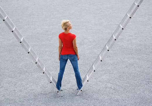 Woman standing outdoors on two ladders : Stock Photo