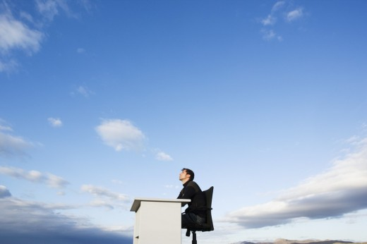 Man sitting at a desk outdoors : Stock Photo
