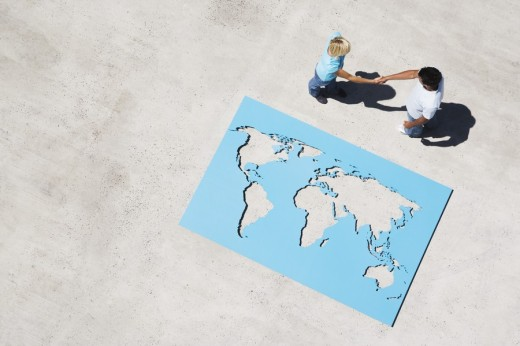 Aerial View of man and woman shaking hands with world map outdoors : Stock Photo
